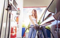 La giovane donna graziosa rifornisce di carburante l'automobile fotografie stock libere da diritti