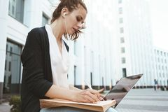 La giovane donna graziosa scrive con una penna sul documento cartaceo e sulle informazioni di ricerca in Internet sul computer po Immagine Stock Libera da Diritti
