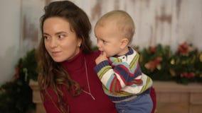 La giovane donna graziosa scuote il bambino nelle sue armi che stanno vicino all'albero di Natale e che mostrano le decorazioni l video d archivio