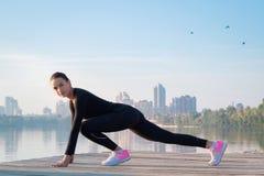La giovane donna graziosa si esercita sul pilastro durante il workou di sport di mattina Fotografia Stock