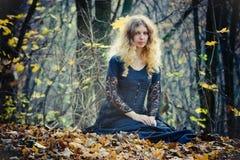 La giovane donna graziosa si siede nel legno fotografie stock