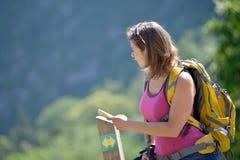 La giovane donna graziosa sta facendo un'escursione in montagne Fotografia Stock