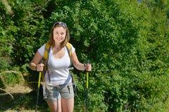 La giovane donna graziosa sta facendo un'escursione in montagne Fotografie Stock