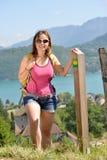 La giovane donna graziosa sta facendo un'escursione in montagne Fotografie Stock Libere da Diritti