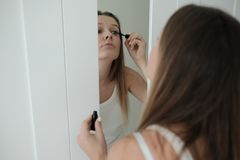La giovane donna graziosa sta finendola per comporre immagini stock