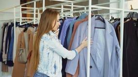 La giovane donna graziosa sta parlando sul telefono cellulare e sta comperando per i vestiti in boutique lussuoso Sta esaminando  stock footage