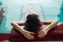La giovane donna graziosa sta rilassandosi nella piscina nel complesso della stazione termale, concetto della località di soggior Fotografia Stock