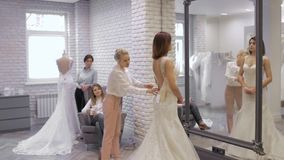 La giovane donna graziosa sta scegliendo un vestito da sposa nel negozio ed il commesso sta aiutandola Gruppo di ragazze dentro stock footage