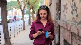 La giovane donna graziosa utilizza uno smartphone per traversare sulla via archivi video