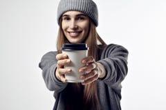 La giovane donna graziosa in vestiti grigi tiene una tazza di carta del caffè Porti via il pacchetto per la disposizione Fuoco su Immagini Stock