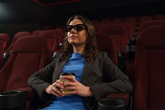 La giovane donna guarda il film 3D al cinema e beve il caffè, lo Immagine Stock Libera da Diritti