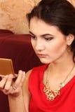 La giovane donna guarda in un piccolo specchietto cosmetico Immagini Stock Libere da Diritti