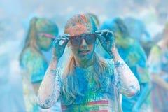 La giovane donna ha coperto di polvere blu di colore che ripara i vetri Immagine Stock