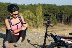 La giovane donna ha ferito la sua gamba dalla caduta fuori la sua bicicletta Fotografia Stock