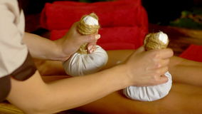 La giovane donna ha massaggio caldo del cataplasma del piede nel salone della stazione termale stock footage