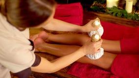 La giovane donna ha massaggio caldo del cataplasma del piede nel salone della stazione termale 4K stock footage