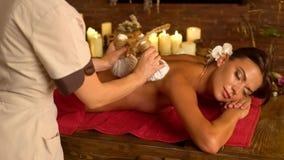 La giovane donna ha massaggio caldo del cataplasma nel salone della stazione termale archivi video