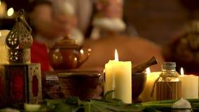 La giovane donna ha massaggio caldo del cataplasma nel salone della stazione termale con le candele brucianti video d archivio