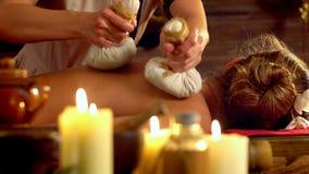 La giovane donna ha massaggio caldo del cataplasma nel salone della stazione termale con le candele brucianti stock footage