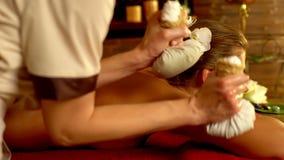 La giovane donna ha massaggio esotico caldo del cataplasma nel salone della stazione termale 4K stock footage