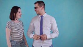 La giovane donna ha messo la protesi acustica nell'uomo allegro dell'orecchio su fondo blu archivi video