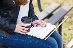 La giovane donna ha pausa caffè che si siede con il computer portatile Fotografia Stock