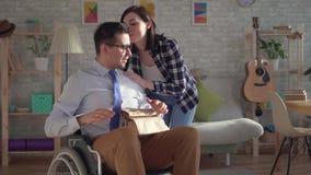La giovane donna ha riunito il pranzo per il suo marito disabile in una sedia a rotelle stock footage