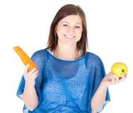 La giovane donna ha scelto fra la mela e la carota sopra fondo bianco Fotografie Stock Libere da Diritti