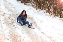 La giovane donna ha slittato e caduto nella strada della neve immagine stock libera da diritti
