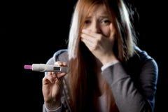 La giovane donna ha spaventato e colpito il risultato positivo del test di gravidanza della tenuta che sembra infelice Fotografia Stock Libera da Diritti