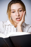 La giovane donna ha stupito da che cosa sta leggendo Fotografie Stock Libere da Diritti