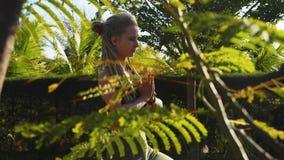 La giovane donna ha una pratica di meditazione che si siede nella posa del loto con le mani del namaste video d archivio