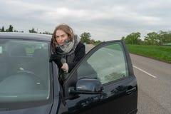 La giovane donna ha una ripartizione dell'automobile e spinge la sua automobile via immagini stock libere da diritti