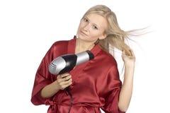 La giovane donna ha vestito l'accappatoio rosso usando l'asciugacapelli Fotografie Stock