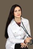 La giovane donna il medico in un'uniforme medica di bianco con una stanza Immagine Stock Libera da Diritti