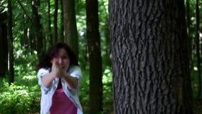 La giovane donna imita la fucilazione nella foresta stock footage