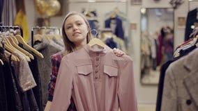 La giovane donna incantante prova su un vestito e sull'esaminare la macchina fotografica in un negozio dell'abbigliamento archivi video