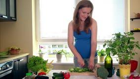 La giovane donna incinta che affetta la paprica verde e la assaggia che esamina la macchina fotografica archivi video