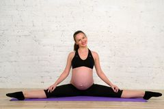 La giovane donna incinta che fa allungando la cordicella si esercita sulla stuoia di yoga Fotografia Stock
