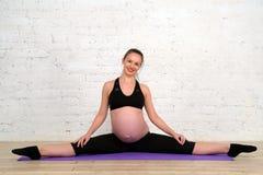 La giovane donna incinta che fa allungando la cordicella si esercita sulla stuoia di yoga Immagine Stock