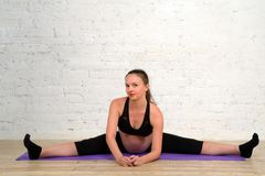 La giovane donna incinta che fa allungando la cordicella si esercita sulla stuoia di yoga Immagine Stock Libera da Diritti