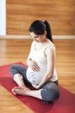 La giovane donna incinta che si siede su una stuoia della palestra, abbracciando la sua pancia, yoga di pratica posa Fotografia Stock