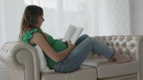 La giovane donna incinta con capelli ricci sta trovandosi sullo strato stock footage