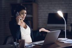 La giovane donna incinta sta parlando sul telefono allo scrittorio nell'ambiente scuro Donna incinta che lavora al computer porta Immagine Stock