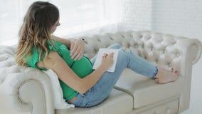 La giovane donna incinta sta scrivendo in un diario che si trova sul sofà vicino alla grande finestra stock footage