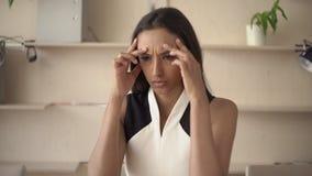 La giovane donna indiana del ritratto soffre dall'emicrania nell'ufficio stock footage