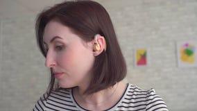 La giovane donna inserisce una protesi acustica nel suo orecchio stock footage