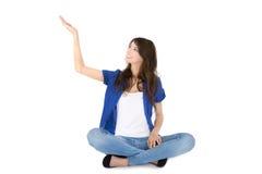La giovane donna isolata che si siede in gambe attraversate sta presentando. Immagine Stock