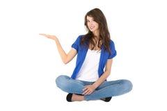 La giovane donna isolata che si siede in gambe attraversate sta presentando. Fotografie Stock