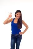 La giovane donna ispanica attraente nella cima casuale ed i jeans che sorridono dare felice e allegro sfogliano su Fotografia Stock